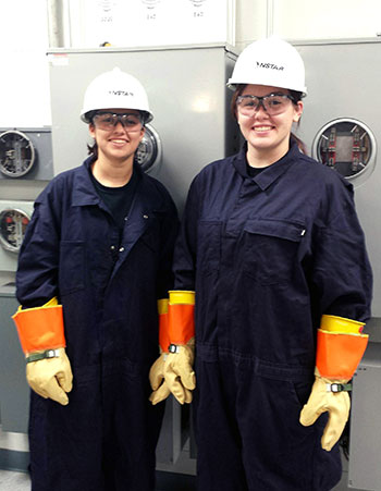 Haley Hughes (right) and Kristen Sabino stand in the meter training room at an NStar learning facility. The two are part of an apprenticeship program with the utility company, something economists say the U.S. needs more of in order to fill open trade jobs. Courtesy of Earl Benders