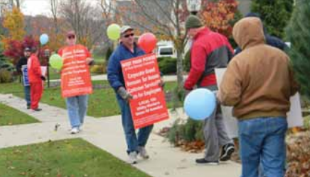 FirstEnergy President and Chief Executive Officer Tony Alexander could not escape from UWUA members demonstrating at his home, pictured here contrasting his multi-million dollar salary with their own